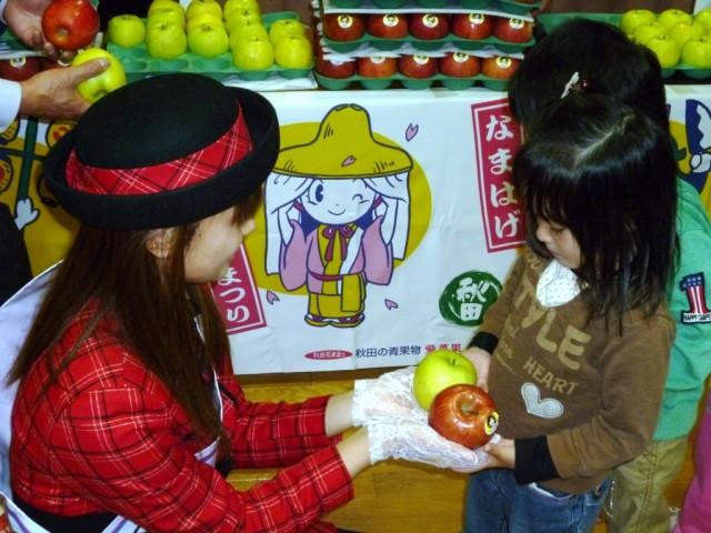 『ミスりんご』小松有沙さんからからりんごをもらう園児